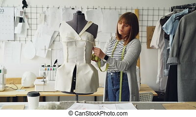 Young seamstress is measuring clothing pinned to tailoring...
