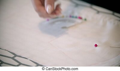 Young seamstress making marks using the soap and form. Mid shot
