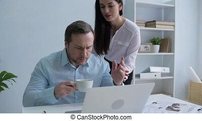Young secretary massaging back of her boss in office -...