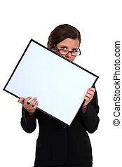 young secretary with glasses lowered holding white board
