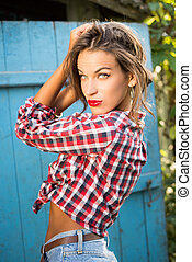 Young seductive pretty girl in shirt and jeans