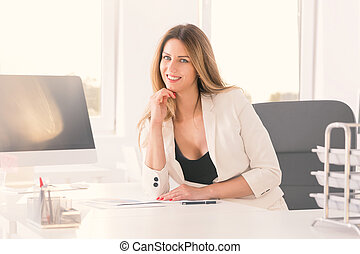 Young self-confident businesswoman in her office