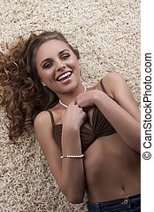 young sensual brunette in bra over carpet