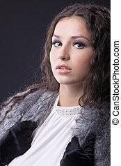 Young sensual girl close-up portrait in fur coat