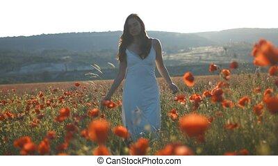 Young sensual girl walk among poppy flower in field