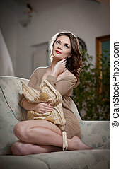 Young sensual woman sitting on sofa