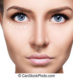 Young sensual woman with cream dots on face.