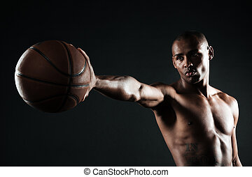 Young serious basketball player holding ball with one hand