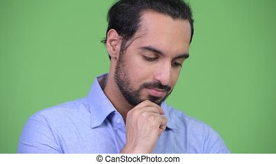 Young serious bearded Indian businessman thinking - Studio...
