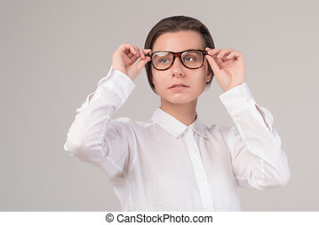 Young serious business girl puts on glasses