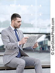 young serious businessman newspaper outdoors