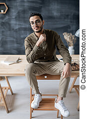 Young serious businessman sitting on wooden table with his feet on chair i