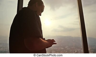 Young serious businessman using a smartphone next to window at amazing sunset and beautiful city view. slow motion.
