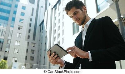 Young serious businessman using his tablet in the street. Great summer day, outdoors.