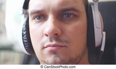 Young serious caucasian man has blue eyes working on...