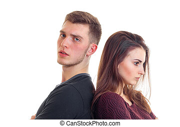 young serious guy with a girl stand each other back close-up