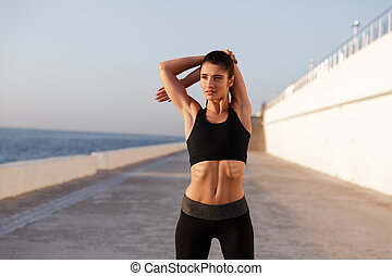 Young serious healthy woman stretching and training in morning