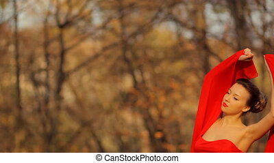 Young serious lady wearing long beautiful red dress posing on camera in a park.