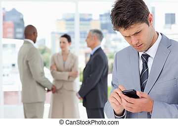 Young serious manager using his cell phone to send a text -...