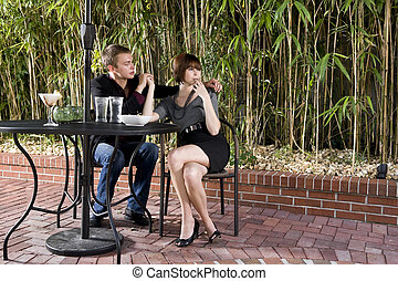 Young serious romantic couple dining on patio