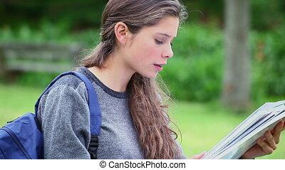 Young serious woman reading a notebook
