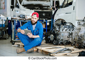 Young serious worker or technician in workwear surfing in the net