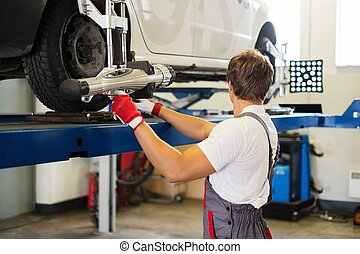 Young serviceman checking wheel alignment in a car workshop