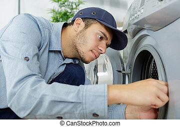 young serviceman working on washing machine
