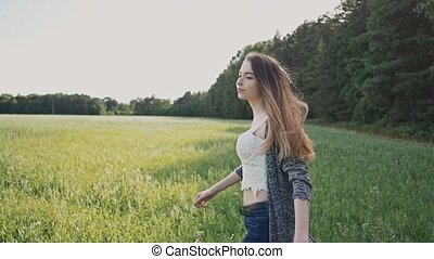 Young sexy and attractive girl walks the field in beautiful purple sunset rays. Summer. The youth. Freedom.