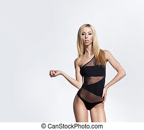 Young, sexy and beautiful woman in swimsuit over white background