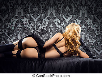 Young, sexy and beautiful woman in underwear in the bed over...