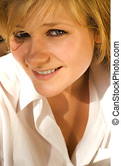 Young sexy beautiful tanned blond woman in white coat