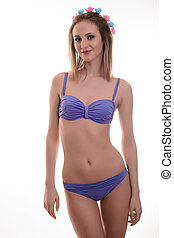 Young sexy beautiful woman in purple swimsuit isolated on the white background