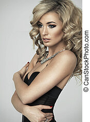 Young sexy blond woman in black lingerie posing on studio