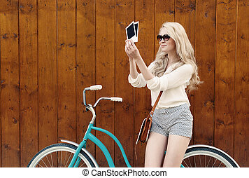 young sexy blond woman standing near a green vintage bicycle holding photos and smiling, warm, tonning
