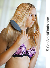 Young sexy blond woman with comb