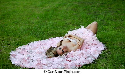young sexy blonde girl in pink elegant dress lying on the green lawn