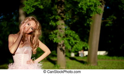 young sexy blonde girl in pink elegant dress standing in the woods