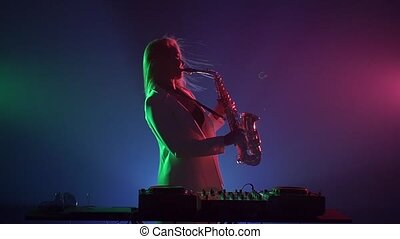 Young sexy, blonde woman dj, bending, in white jacket and black top playing music using saxophone, flipping hair, leans back, dancing, on green, pink and blue, backlight, slow motion