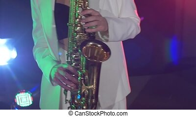 Young sexy, blonde woman dj in white jacket and black top playing music using saxophone, flipping hair, dancing, cam moves upwards, slow motion