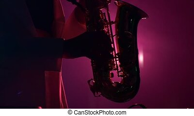 Young sexy, blonde woman dj in white jacket and black top playing music using saxophone, flipping hair, on dark pink, dancing, silhouette, slow motion