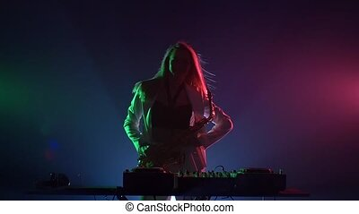 Young sexy, blonde woman dj, in white jacket and black top playing music using saxophone, flipping hair, dancing, hands up, claps, cam moves upwards, on green, pink and blue, backlight, slow motion