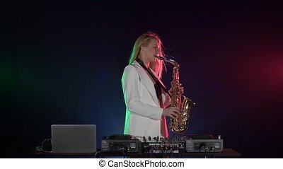 Young sexy, blonde woman dj in white jacket playing music using saxophone on black, slow motion