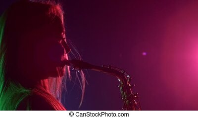 Young sexy, blonde woman dj in white jacket and black top playing music using saxophone, flipping hair, dancing, leans back, on pink, silhouette, slow motion