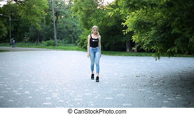 Young sexy blonde woman with very long hair is walking in the park. Moves towards the camera