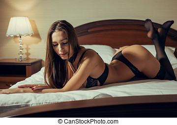 Young sexy brown-haired woman lies in bed in beautiful black underwear.