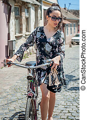 Young sexy brunette girl with old retro style vintage bicycle