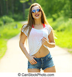 Young sexy brunette woman portrait in sunglasses. Stylish woman posing with interested look. Outdoors. Urban lifestyle shot.