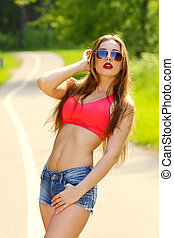 Young sexy brunette woman portrait. Stylish woman posing with interested look and sunglasses. Summer Modern Youth Lifestyle.