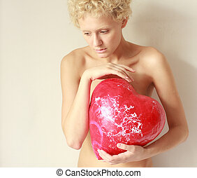 Young sexy girl holding a big toy red heart, in gentle tones